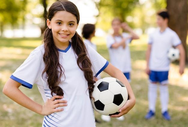 Menina posando com uma bola de futebol do lado de fora