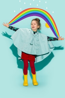 Menina posando em estilo de moda, vestindo roupas de outono em fundo azul. botas de borracha amarela.