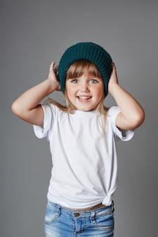 Menina posando em um fundo cinza, emoções brilhantes e alegres no rosto da menina, a criança fazendo caretas e poses