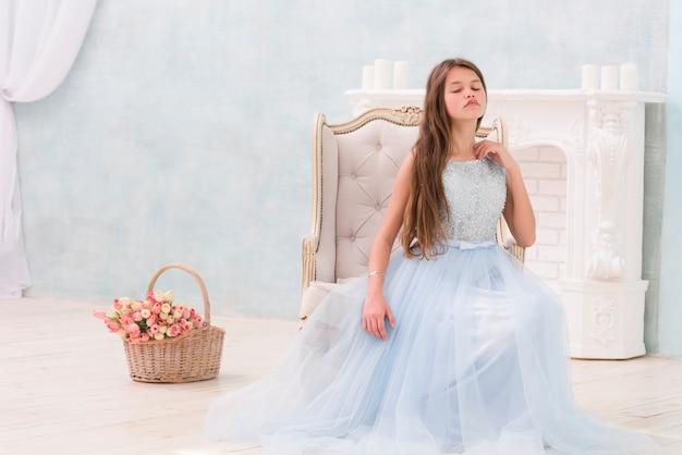 Menina posando enquanto está sentado na poltrona perto de cesta de flores
