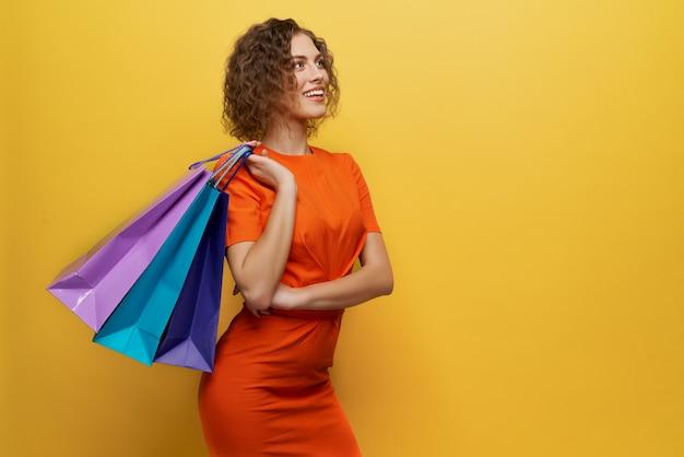 Menina positiva com cabelo curto, mantendo sacos de papel colorido