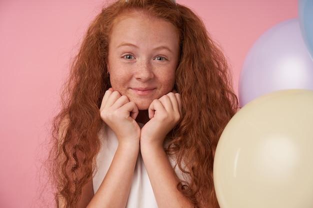 Menina positiva com cabelo ruivo cacheado e vestido branco comemora algo, expressa verdadeiras emoções positivas, olhando para a câmera alegremente e apoiando a cabeça nas mãos, posando sobre um fundo rosa