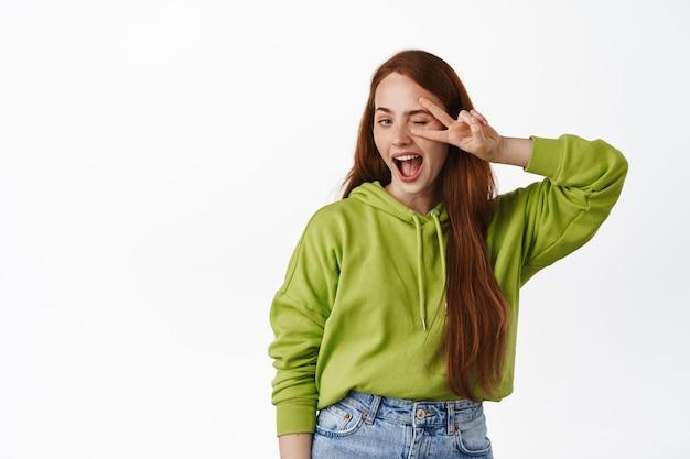 Menina positiva com cabelo ruivo longo natural, mostra o gesto do sinal v de paz perto de um olho piscando, sorrindo feliz, posando com roupa casual em branco.