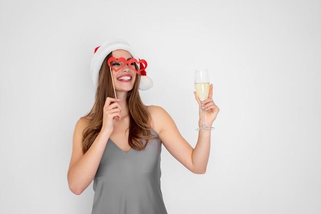 Menina positiva com chapéu de natal usando óculos escuros de mentira segurando taça de champanhe na festa de ano novo