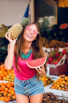 Menina positiva com um grande sorriso segurando ananás e uma fatia de melancia no mercado