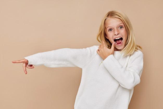 Menina positiva com um suéter fazendo caretas no conceito de estilo de vida de crianças
