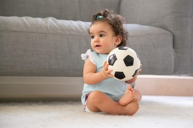 Menina positiva de cabelo preto com roupas azul claro, sentada no chão em casa, olhando para longe, jogando bola de futebol. copie o espaço. criança em casa e conceito de infância