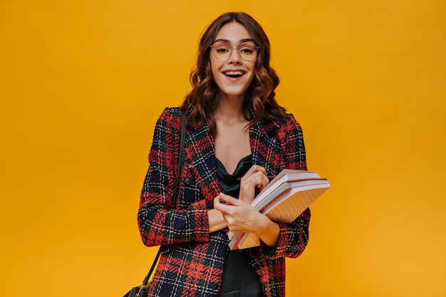 Menina positiva de óculos e jaqueta listrada sorrindo na parede amarela
