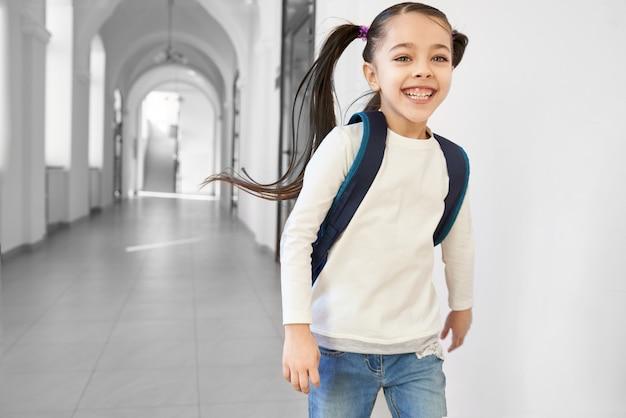 Menina positiva e feliz da escola que corre para dirigir do corredor e do sorriso da escola.
