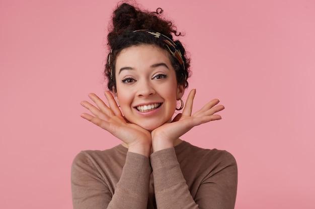Menina positiva, mulher feliz com coque de cabelo encaracolado escuro. usando bandana, brincos e suéter marrom. tem maquiagem. mantém as palmas das mãos sob o queixo