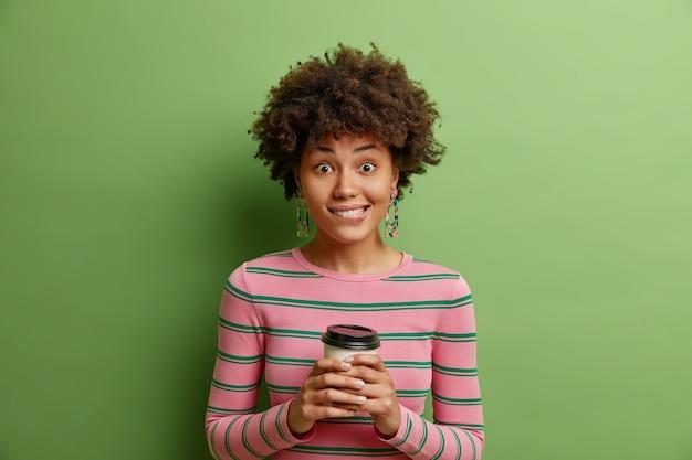 Menina positiva segurando xícara de café morde lábios olha alegremente para a câmera e conversa agradável com interlocutor usa macacão listrado e brincos isolados na parede verde