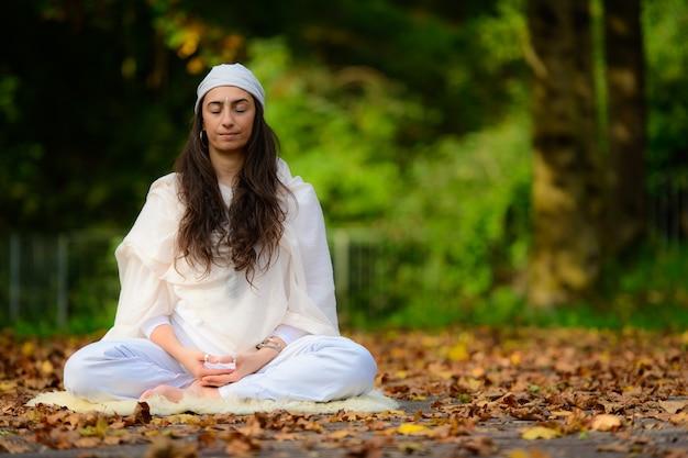 Menina praticando ioga entre as folhas de outono