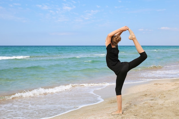 Menina praticando ioga na praia
