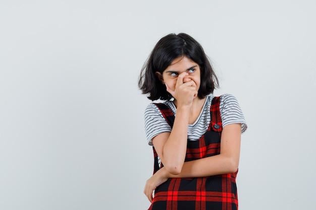 Menina pré-adolescente cobrindo a boca e o nariz com a mão enquanto desvia o olhar com a camiseta