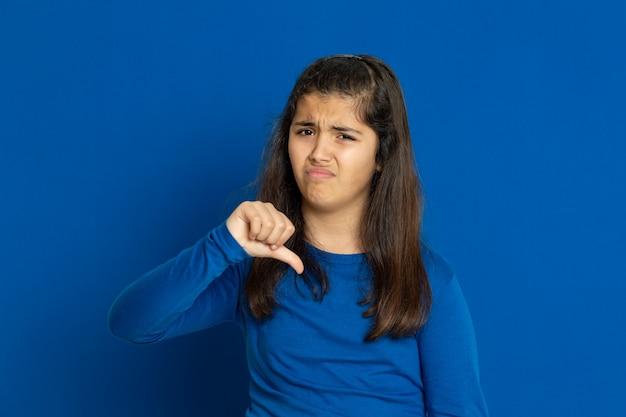 Menina pré-adolescente com camisa azul, gesticulando sobre parede azul