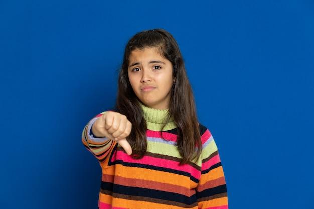 Menina pré-adolescente com camisa listrada, gesticulando sobre parede azul