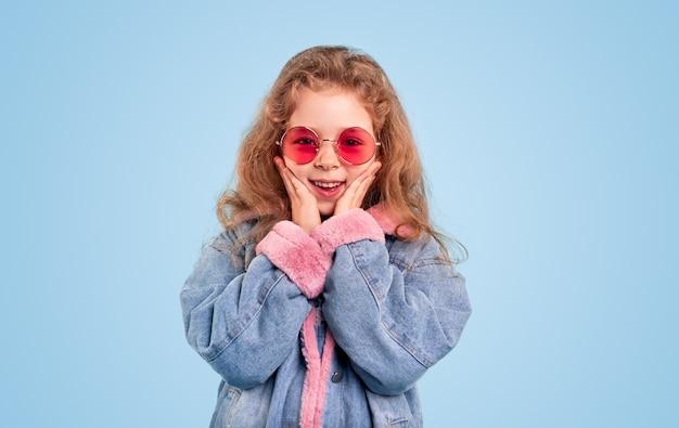 Menina pré-adolescente encantadora e maravilhada com uma jaqueta jeans quente e óculos de sol rosa da moda tocando o rosto e sorrindo em pé