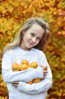Menina pré-adolescente feliz com tangerina fresca no outono