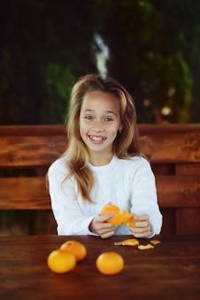 Menina pré-adolescente feliz descascando tangerina fresca