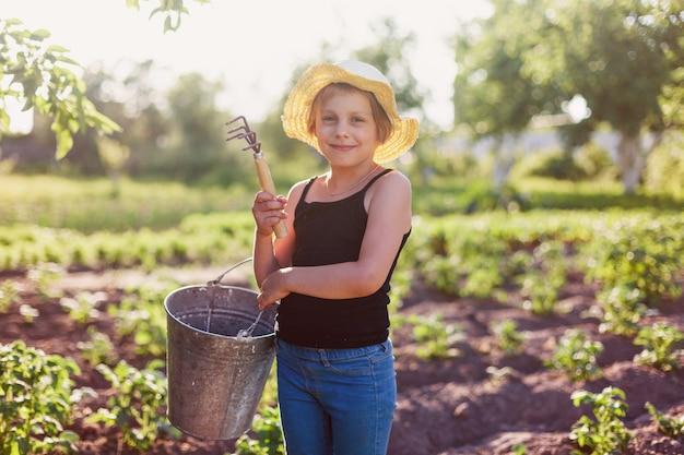 Menina pré-adolescente na superfície de um jardim de verão com ferramentas para trabalhar no jardim
