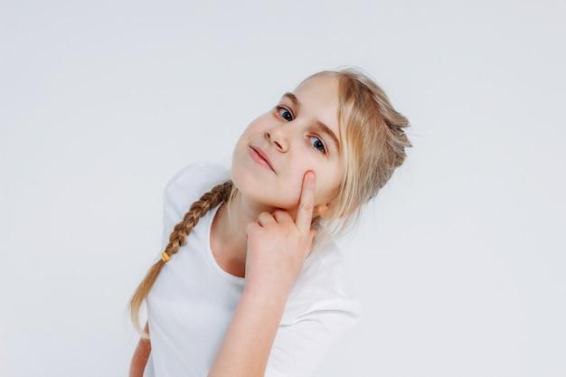 Menina pré-adolescente olha para a câmera e segura a mão no rosto, isolado no fundo branco