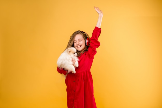 Menina pré-adolescente segurando um cachorro pequeno em suas mãos