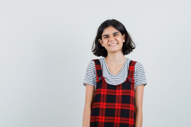 Menina pré-adolescente sorrindo em t-shirt, macacão e parecendo alegre. vista frontal. espaço para texto