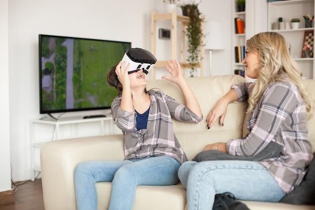Menina pré-escolar alegre usando fone de ouvido de realidade virtual, enquanto sua mãe está sentada ao lado dela no sofá.