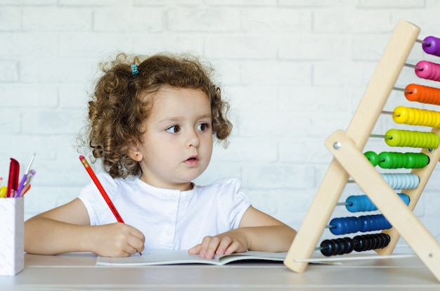 Menina pré-escolar aprendendo matemática. criança está contando com as contas. desenvolvimento, educação, ensino e formação de crianças.
