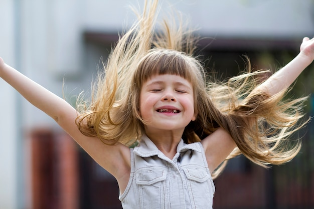 Menina pré-escolar bonita no vestido branco sem mangas, com belos cabelos loiros compridos soprada pelo vento, sorriso desdentado engraçado e braços abertos
