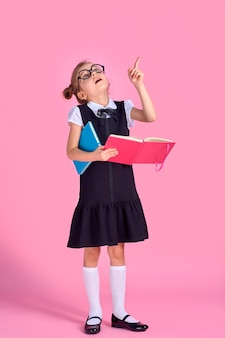 Menina pré-escolar com óculos, segurando um livro, erguendo a mão e o dedo em um espaço rosa