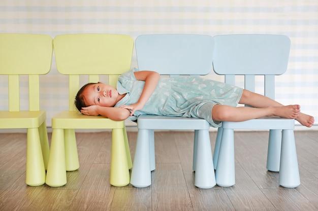 Menina pré-escolar da criança do retrato em uma sala do jardim de infância que encontra-se na cadeira plástica do bebê.