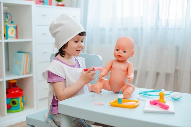 Menina pré-escolar de 3 anos de idade brincando de médico com boneca. a criança faz um brinquedo de injeção.