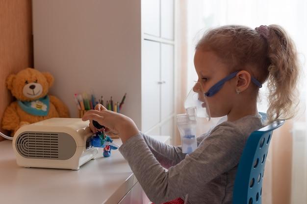 Menina pré-escolar fazendo inalação com nebulizador em casa conceito de gripe e resfriado