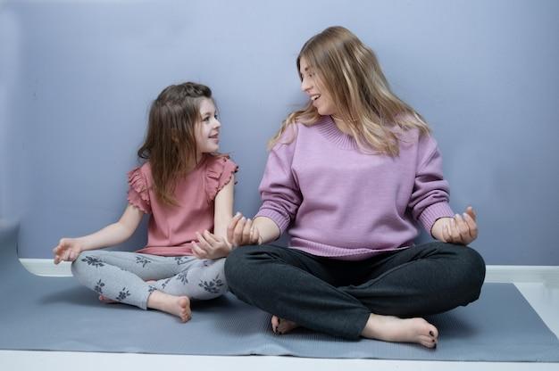 Menina pré-escolar feliz caucasiana com mãe loira grávida fazendo ioga em casa juntos