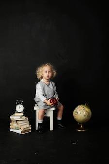 Menina pré-escolar feliz com livros, globo e relógio em um fundo preto