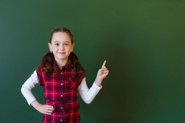 Menina pré-escolar feliz estudante em vestido xadrez em pé na classe perto de um quadro negro verde. conceito de educação escolar