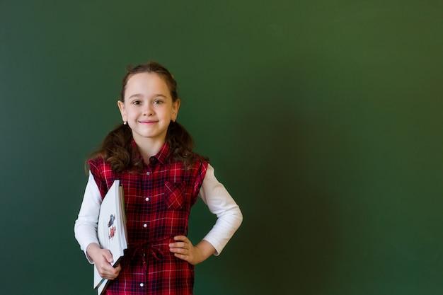 Menina pré-escolar feliz estudante em vestido xadrez em pé na classe perto de um quadro negro verde.