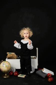 Menina pré-escolar feliz perto do carrinho com livros, globo e relógio em um fundo preto