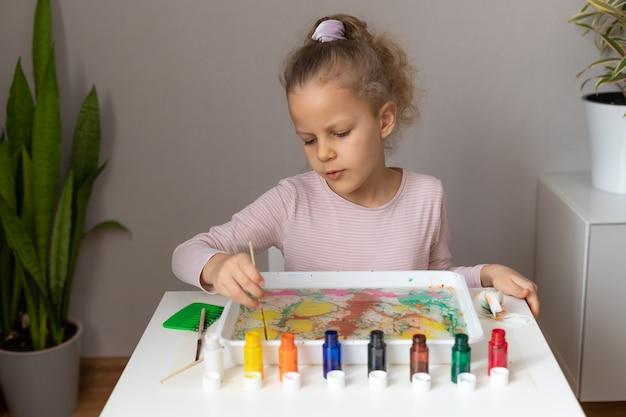 Menina pré-escolar pintando na água. arte ebru