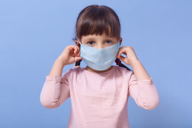 Menina preocupada com cabelos escuros, colocando no rosto máscara médica respirador