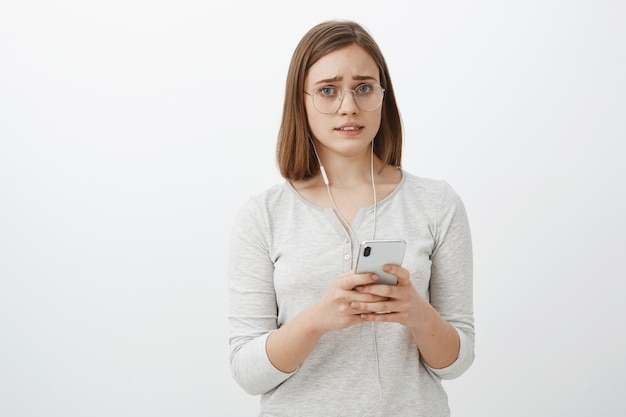 Menina preocupada com um fone de ouvido quebrado. retrato de uma mulher fofa descontente e preocupada de óculos com cabelo castanho curto franzindo a testa e fazendo careta segurando um smartphone usando fones de ouvido