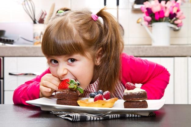 Menina, preparando e comendo bolo com frutas
