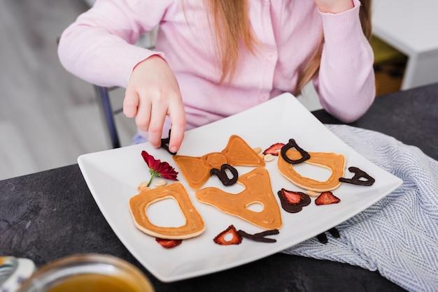 Menina, preparando o café da manhã no dia do pai