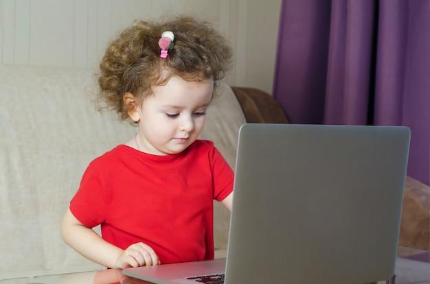 Menina prescooler estudando remotamente on-line sobre auto-isolamento. dependência de jogos de computador em crianças