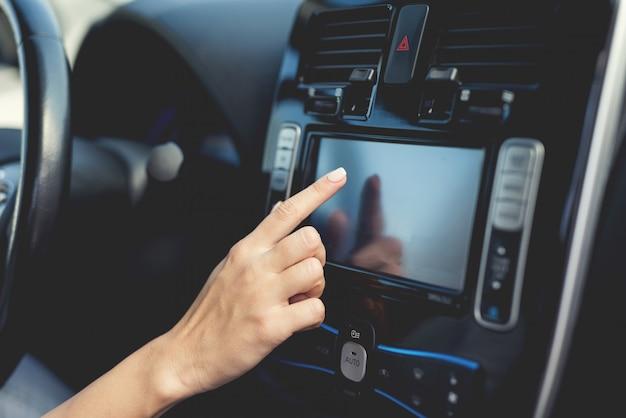 Menina pressiona botões em dispositivos de controle do veículo elétrico.