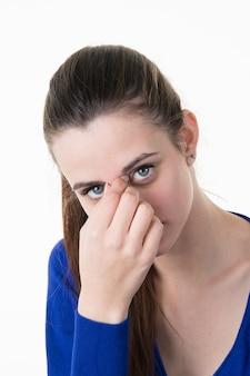 Menina pressionando a parte superior do nariz