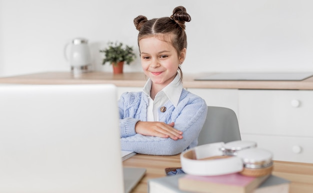 Menina prestando atenção ao professor em uma aula on-line
