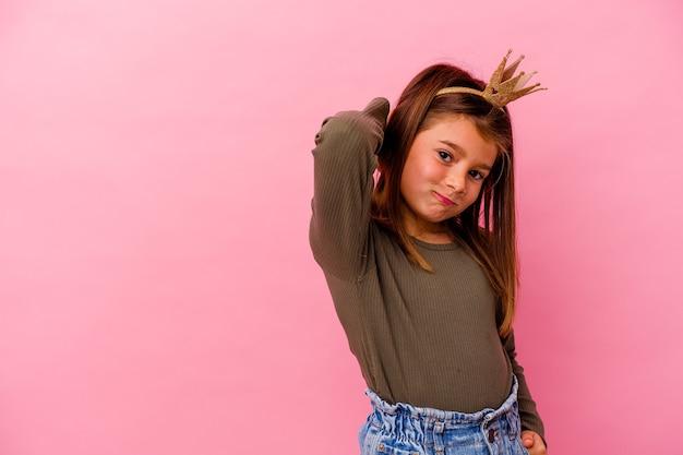 Menina princesa com coroa isolada em fundo rosa, tocando a parte de trás da cabeça, pensando e fazendo uma escolha.