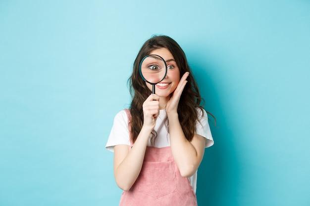 Menina procurando por você. recrutadora de mulher bonita e sorridente olhando pela lupa, olhando para a câmera, investigando, procurando por alguém, em pé sobre um fundo azul